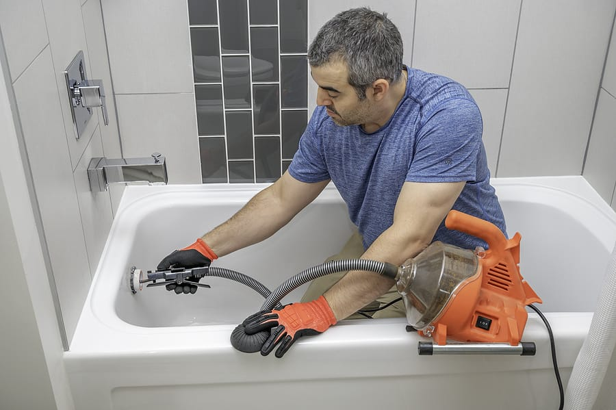 plumber in bathtub using a snake to unclog line